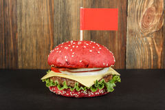 Red cheeseburger with flag close-up. Red cheeseburger with flag on wood background close-up Royalty Free Stock Photography
