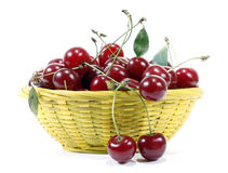 Red cherries. In the yellow basket Stock Photos