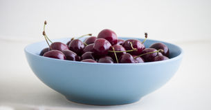 Red cherries in antique bowl Stock Images