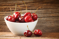 Red cherries in bowl on barn wood Stock Images