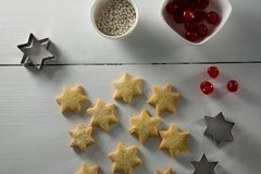 Red cherries in bowl with star shape cookies and cutter. On table Royalty Free Stock Images