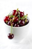 Red cherries in bowl on white background Stock Photos