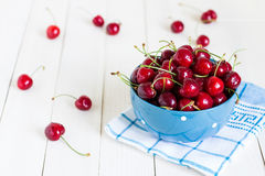 Red cherries in bowl on white wooden background on blue towel Royalty Free Stock Photos