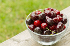 Red cherries in bowl. On wood Stock Images