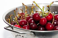 Red cherries on the colander Royalty Free Stock Images