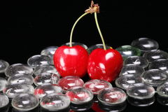 Red cherries and glass beads. A view of two bright red cherries and a pile of glass beads on a black background Stock Photos