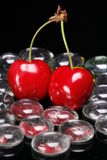 Red Cherries with Glass Beads. Red cherries surrounded by transparent pebbles on reflective black glass Stock Photo