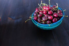 Red cherries in green ceramic bowl on dark background Royalty Free Stock Images