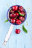 Red cherries in old colander Royalty Free Stock Image