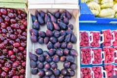 Red cherries, peaches, figs, bananas and raspberries in boxes fo. R sale in local marketplace Stock Images