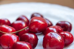 The Red cherries in plate close-up. Close-up Some cherries in white plate stock photo