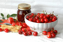 Red cherries, spring temptation. Cherries in a white bowl with a pot of jam, some crackers and a rose royalty free stock photos