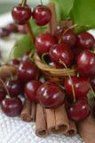 Red cherries with stems and cinnamon rods in front of litlle basket Royalty Free Stock Image