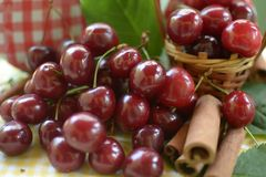 Red cherries with stems and cinnamon rods in front of litlle basket Royalty Free Stock Images