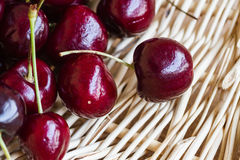Red Cherries. Sweet red cherries on a woven basket Royalty Free Stock Image