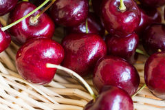 Red Cherries. Sweet red cherries on a woven basket Stock Image