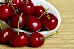 Red cherries in white spoon Royalty Free Stock Image