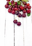 Red cherries on white wooden table  Royalty Free Stock Image