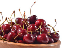Red cherries in a wooden bowl on a white Stock Photography