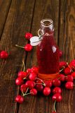 Red cherry drink in bottle in the middle of fruit Stock Photography