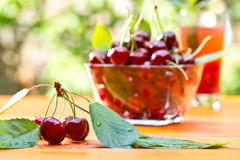 Red cherry and glass of juice Royalty Free Stock Photos