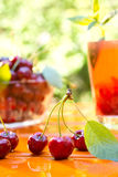 Red cherry and glass of juice Stock Image