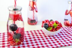 Red Cherry and Grapes on Clear Glass Bottle Royalty Free Stock Photos