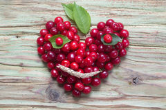 Red cherry heart smiley on wood Royalty Free Stock Photo