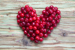 Red cherry heart on wood table Royalty Free Stock Images