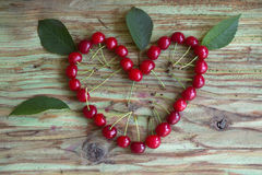 Red cherry heart on wood table Stock Photo