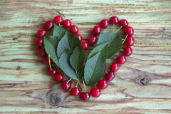 Red cherry heart on wood table Royalty Free Stock Photo
