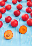 Red cherry plum. Fresh red cherry plum with halves scattered on the table Stock Photography