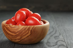 Red cherry plum tomatoes in olive bowl on wood Stock Photo