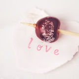 Red cherry sugar coated on a stick with word love Stock Images