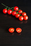 Red cherry tomato on dark wooden table Royalty Free Stock Photos