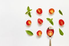 Red cherry tomato, green basil leaves and spoon on white background stock photography