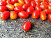 Red cherry tomato, one piece in front of, reader in business, wooden background. One red cherry tomato placed in front of the pieces other on the wooden Stock Images