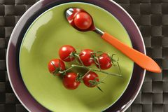 Red cherry tomatoes branch, spoon and green dish. Red tomatoes branchRed cherry tomatoes branch with a spoon on a green dish royalty free stock image