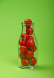 Red cherry tomatoes in glass bottle over green Royalty Free Stock Photos