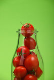 Red cherry tomatoes in glass bottle over green Royalty Free Stock Image