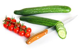 Red cherry tomatoes and green cucumbers Stock Photos