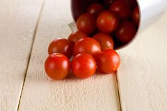 Red cherry tomatoes spilled on white wooden board Royalty Free Stock Image