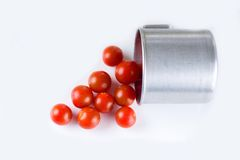 Red cherry tomatoes with water dropes spilled from aluminum cup Royalty Free Stock Photo