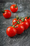 Red cherry tomatoes in water drops. On the black granite surfaces Royalty Free Stock Image