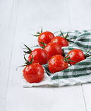 Red cherry tomatoes in water drops on a green linen napkin. On a white colored wooden surface Royalty Free Stock Photos
