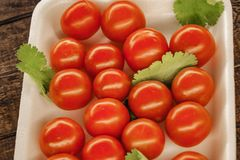 red cherry tomatoes on a white plate with a wooden background stock image