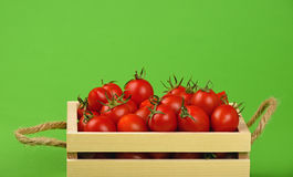 Red cherry tomatoes in wooden box over green Royalty Free Stock Photography