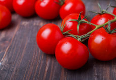 Red cherry tomatoes on the wooden table Royalty Free Stock Photo