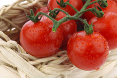 Red cherry tomatoes in a woven basket Stock Image