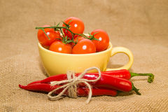 Red cherry tomatoes in a yellow cup and Chile peppers  on old cl Stock Images